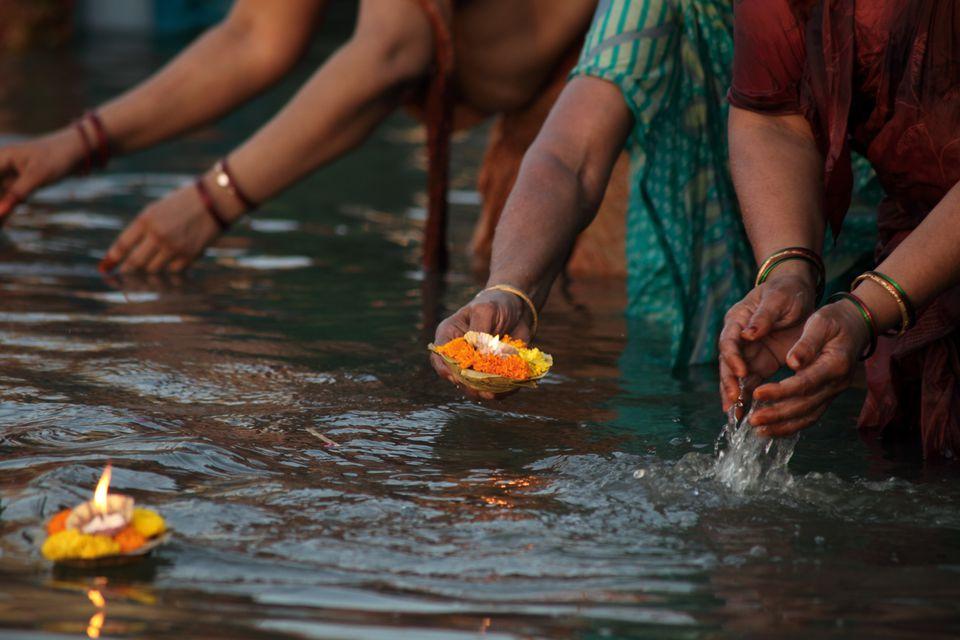 Lighting diyas as offerings to the Ganga River.