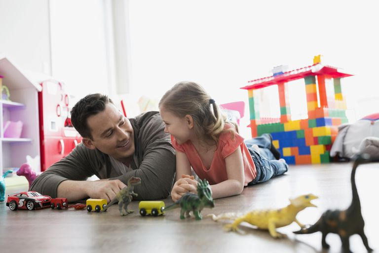 Father and daughter playing with toys on floor