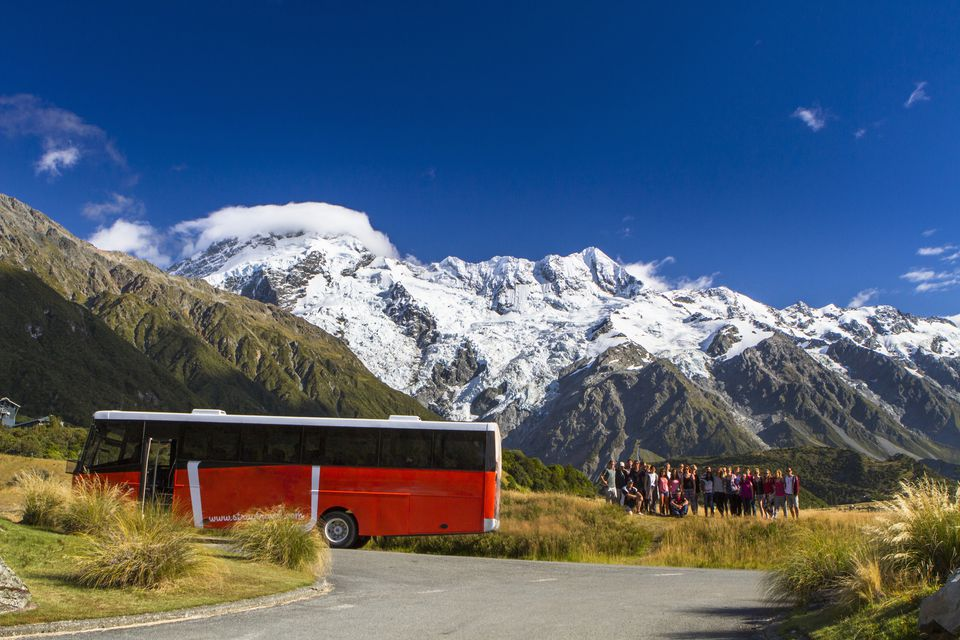 A tour bus stops in front of Mount Cook, New Zealand.