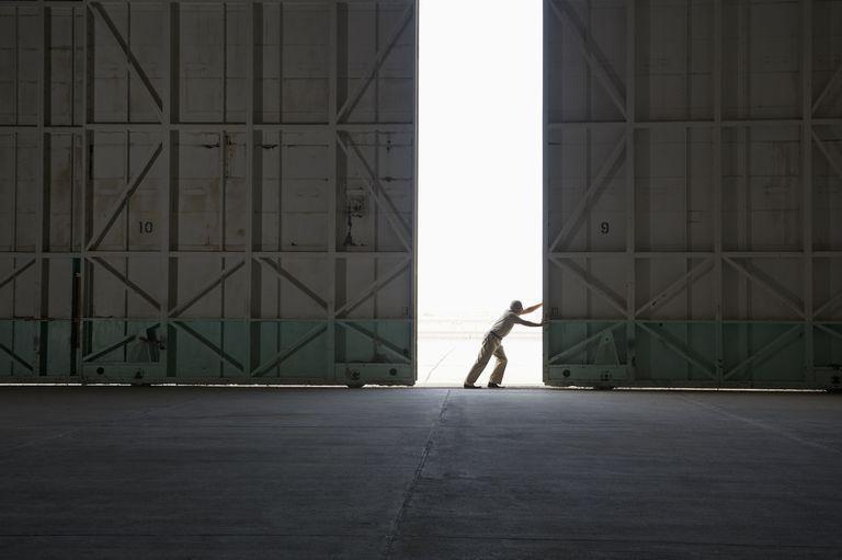 Worker opening large warehouse doors
