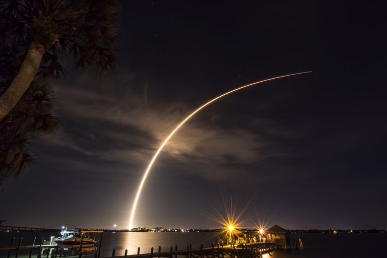 A rocket launches from Cape Canaveral, carrying a communications satellite, over the Indian River Lagoon from Rockledge, Florida