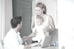 man at computer with woman and baby