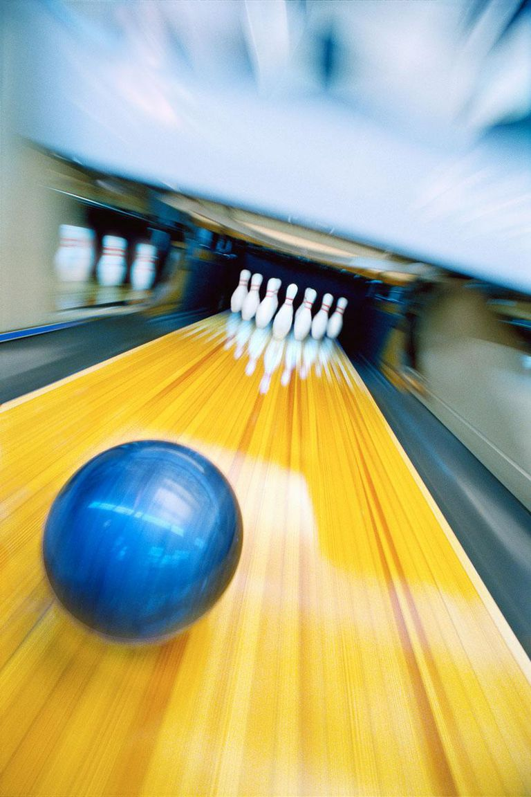 Bowling ball rolling toward pins