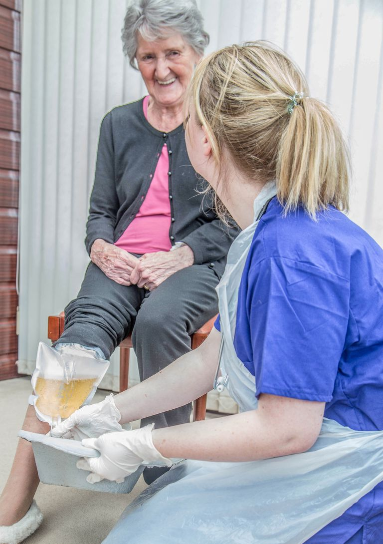 senior woman with catheter nurse emptying catherer with senior woman