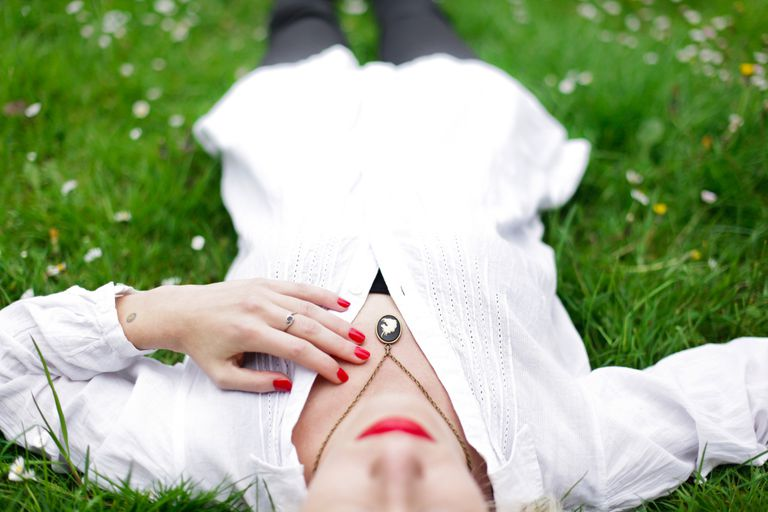 Woman laying in grass with hand on her chest