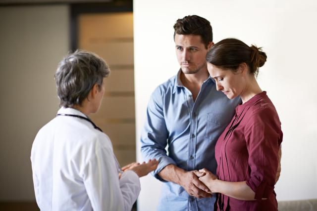 Sad couple with doctor getting news of early miscarriage