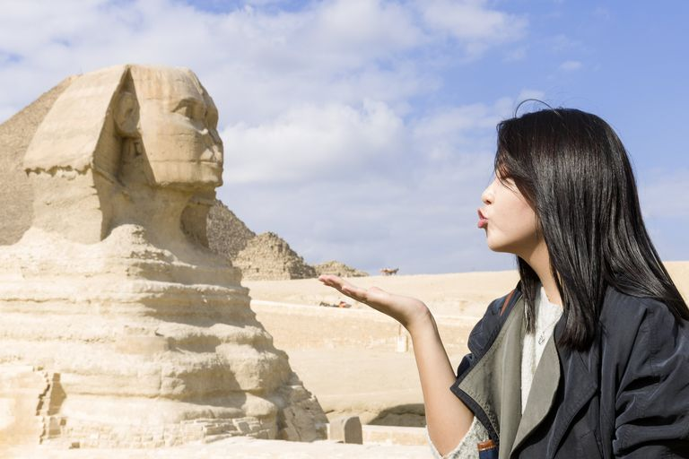 A girl give a photogenic kiss to the great Sphinx in the Giza Necropolis