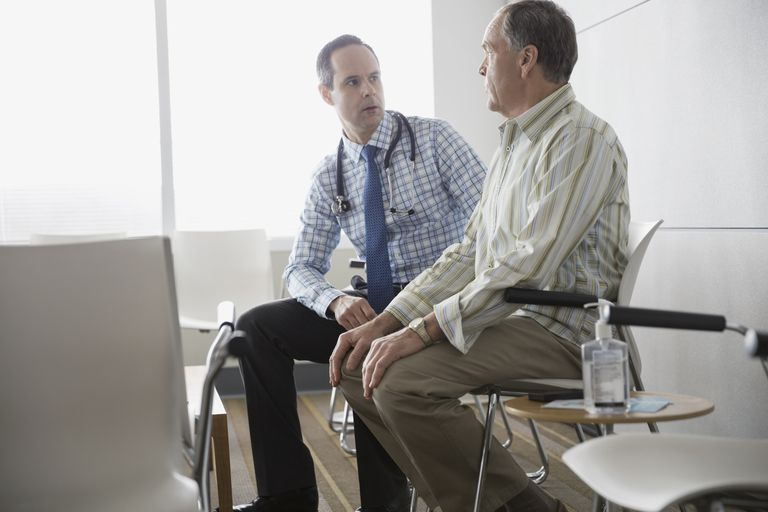 Doctor talking with senior patient in waiting room