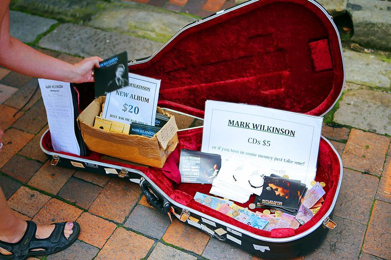 musician's guitar case open with tips and albums for sale
