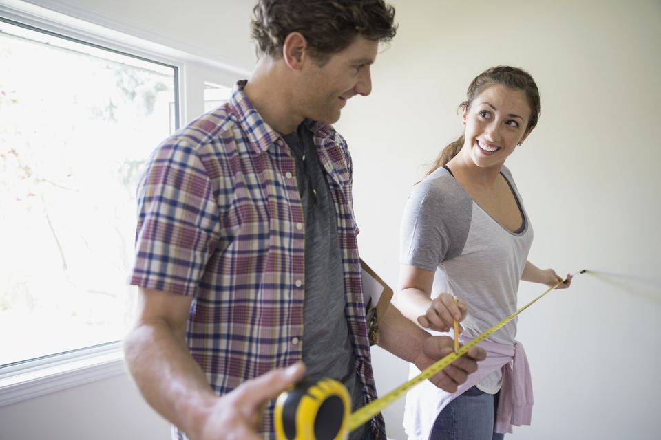 Couple measuring room with tape measure