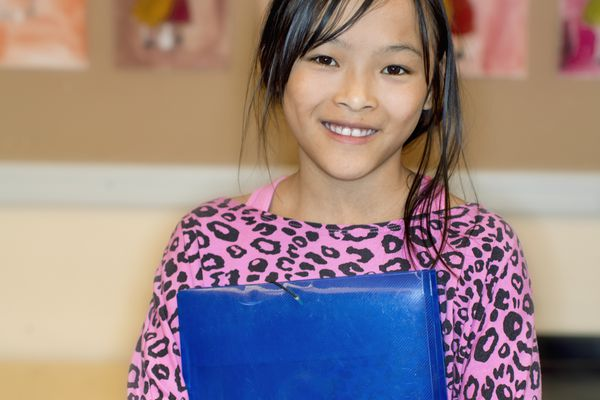 girl with folder in classroom