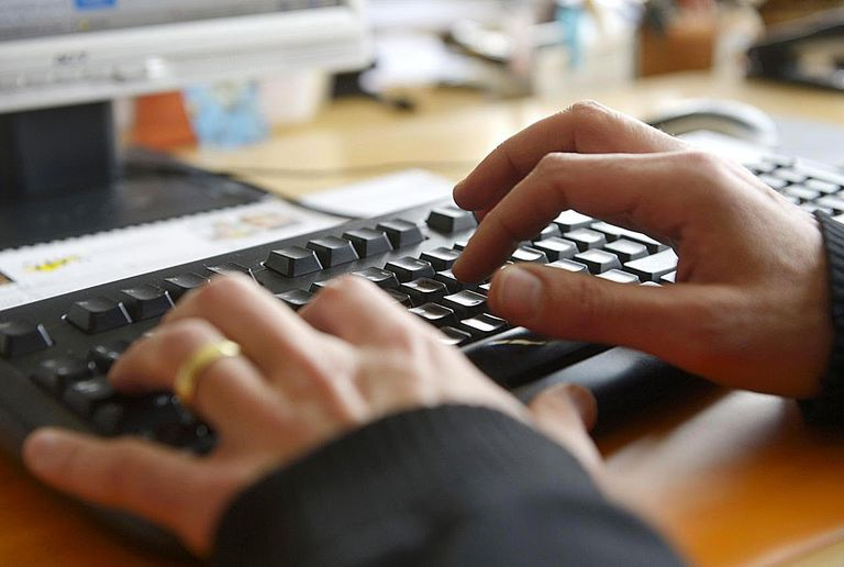 A picture of hands typing on a computer keyboard