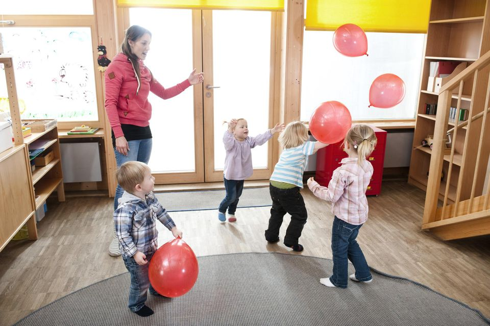 Four kids playing with red balloons
