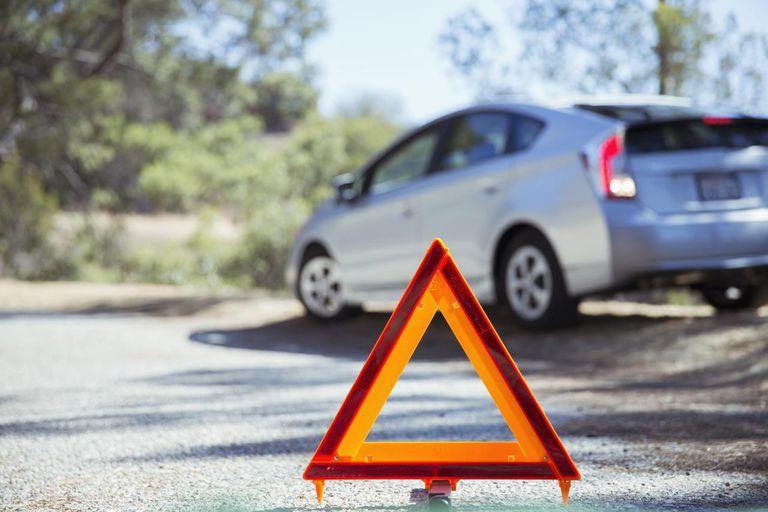 Car at roadside behind warning triangle