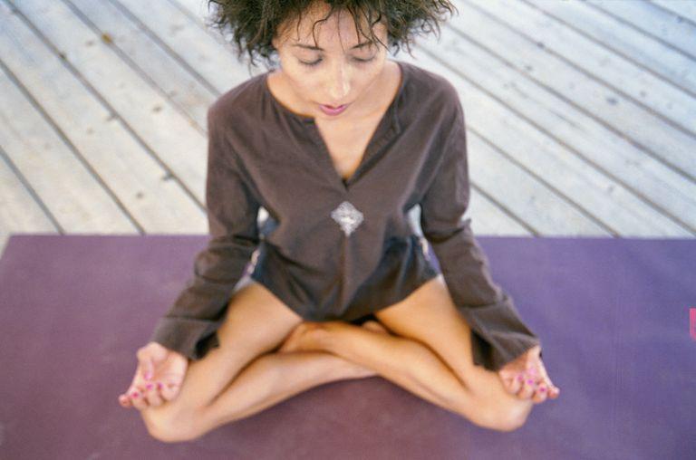 Mujer en posición de loto con ojos cerrados