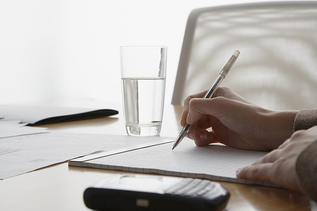How To Write A Successful Executive Summary Businesswomans Hands Writing On Notepad In Boardroom