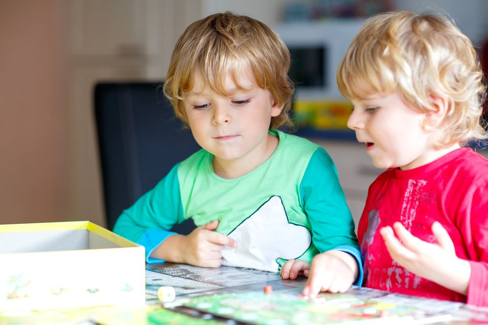 Two little blond kid boys playing together board game at home. Funny siblings having fun.