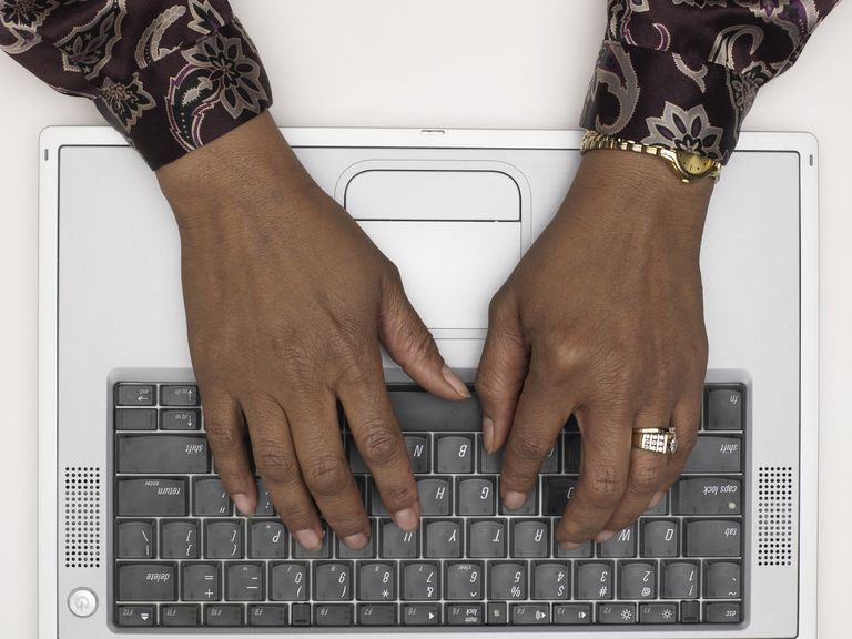 Mature woman using laptop, close-up of hands