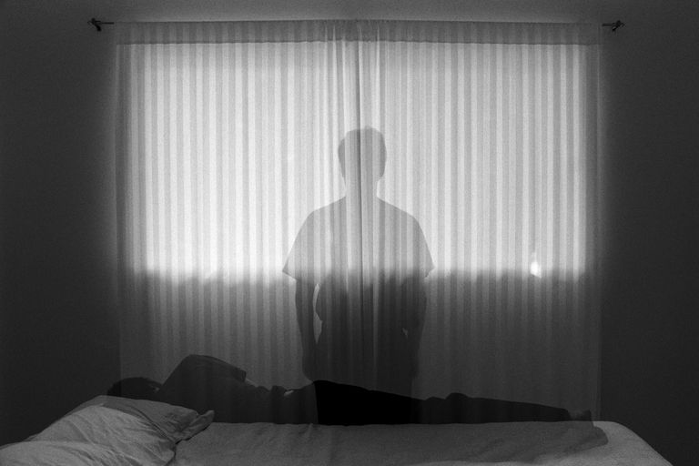 Man sleeping and looking out window (B&W, multiple exposure)