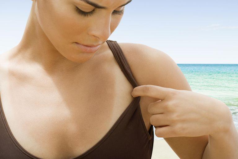 Teenage girl (14-16) looking at tan lines at beach