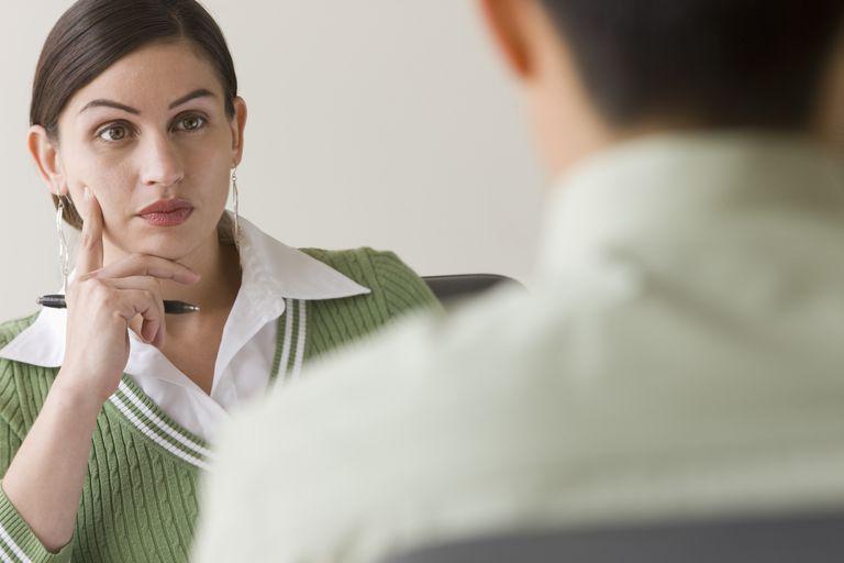 Serious Hispanic businesswoman listening to co-worker