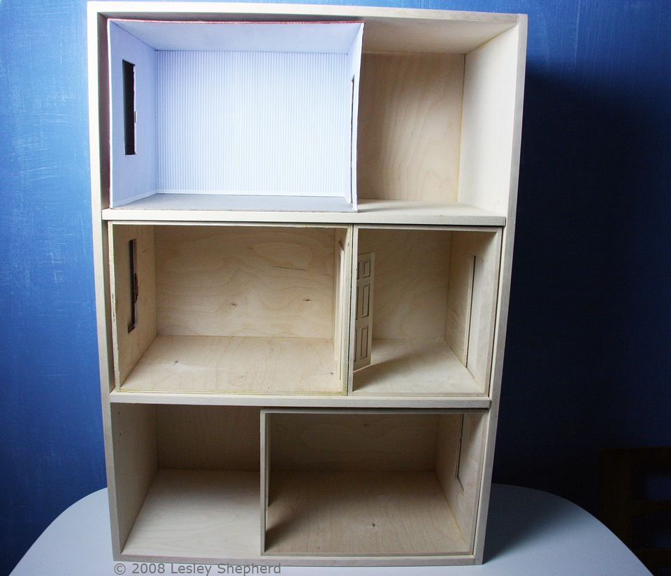 A completed baby house case with two adjustable shelves holds a collection of unfinished roomboxes.