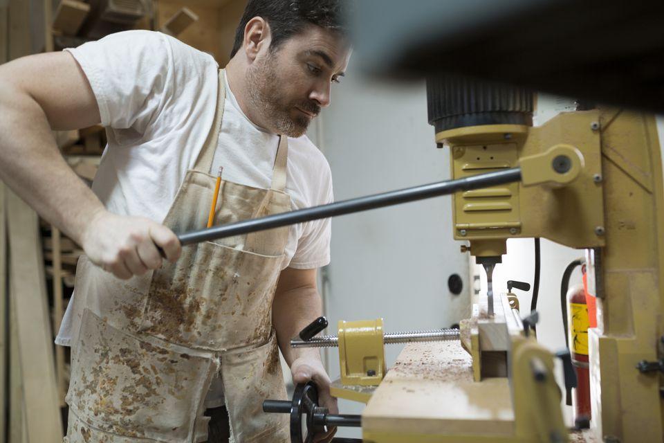Carpenter Using Drill Press in Shop