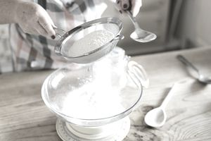 A woman measuring and sifting white flour. Home baking.
