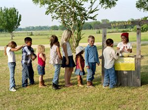 Children (3-11) lining up at lemonade stand, side view