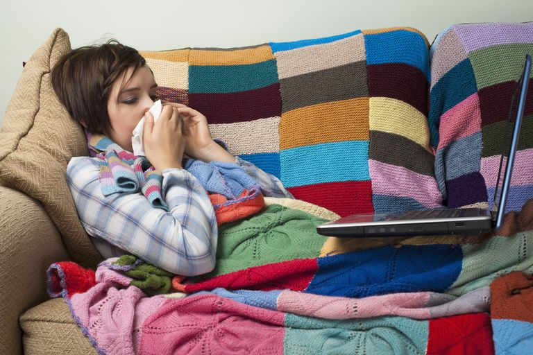 A woman with a cold using a computer.