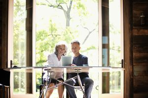 Senior Couple Reading from Digital Tablet at Desk