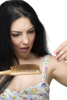 Woman looking at hair in her brush