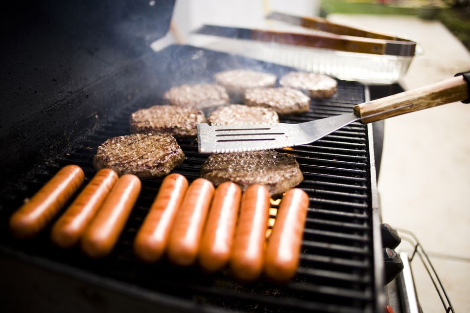 Close up of hamburgers and hot dogs on barbecue grill