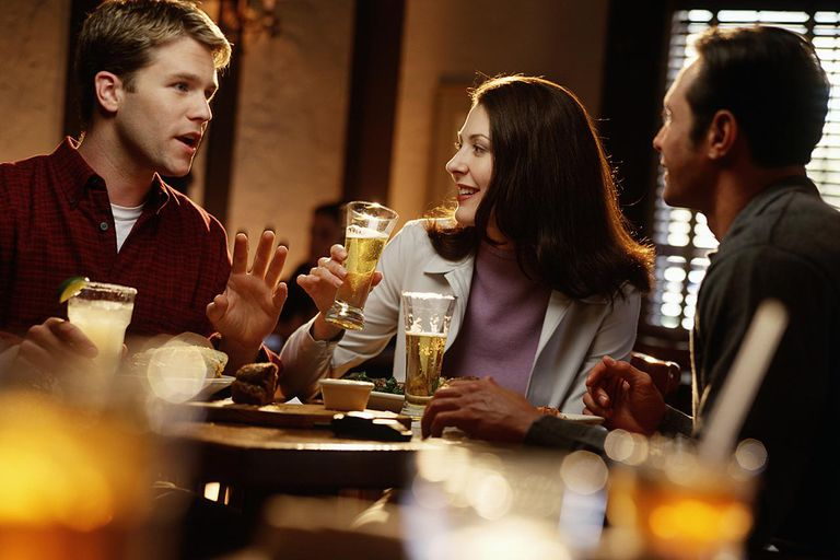 Three friends having meal in restaurant, smiling