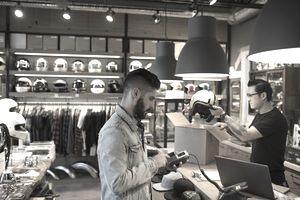 Customer using credit card reader at counter in motorcycle shop