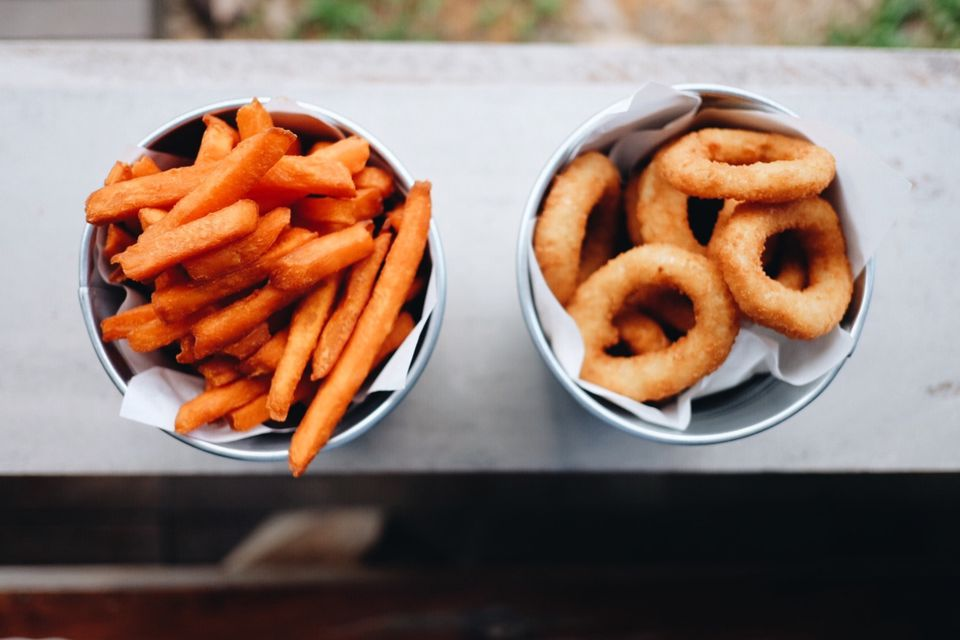 French Fries And Onion Rings In Bowls On Window Sill