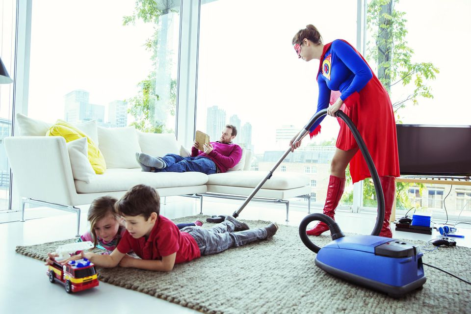 A picture of a mom in a superhero costume vacuuming