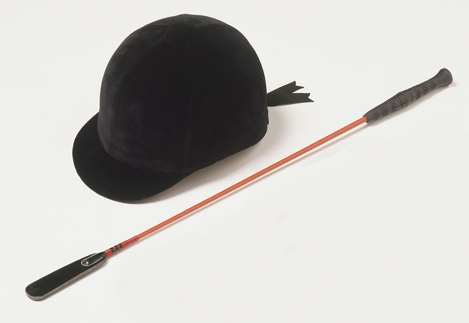 Horse rider's hard hat and whip on white background.