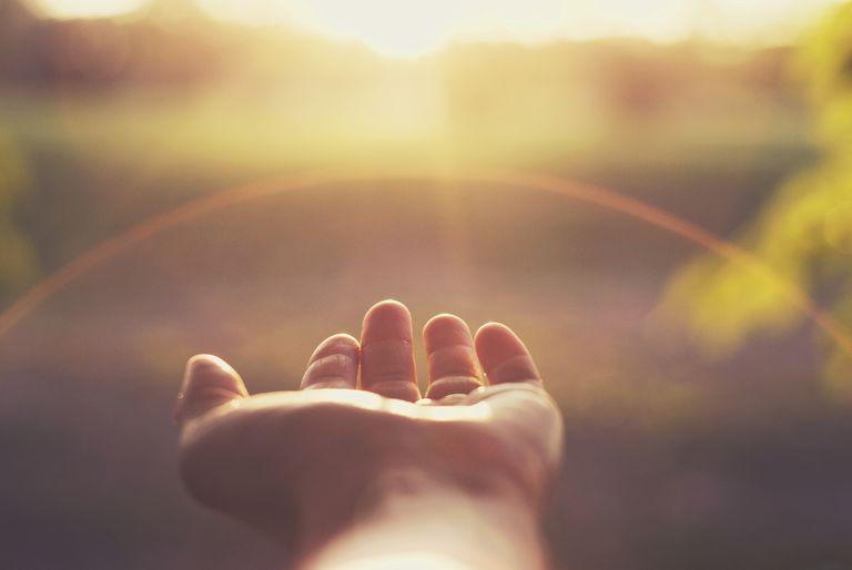 hand reaching out toward the sun
