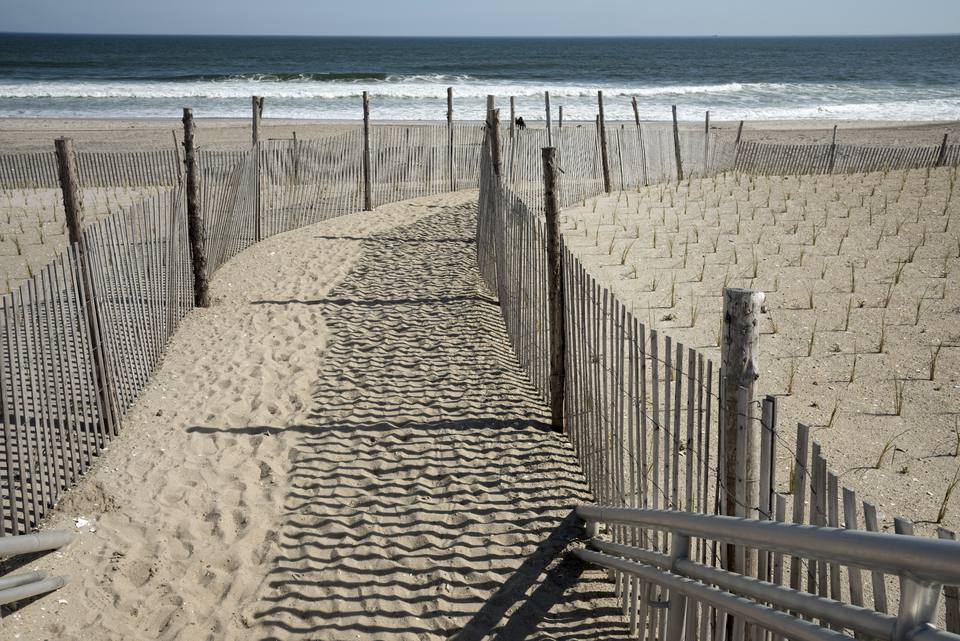 USA, New York State, New York City, Fenced passage on beach at Rockaway Beach