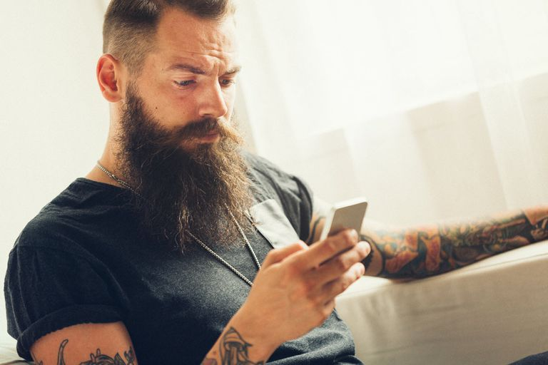 Man looking at iPhone with a confused look on his face.