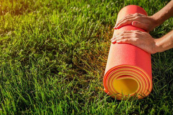 Man rolls yoga mat on the grass