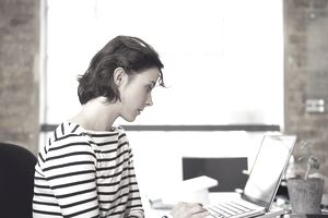 A young woman works on laptop