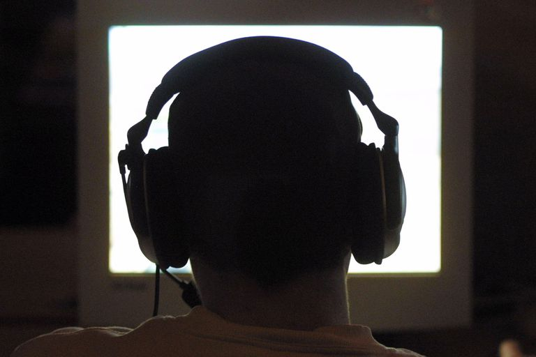 Silhouette of head with large headphones in computer glow