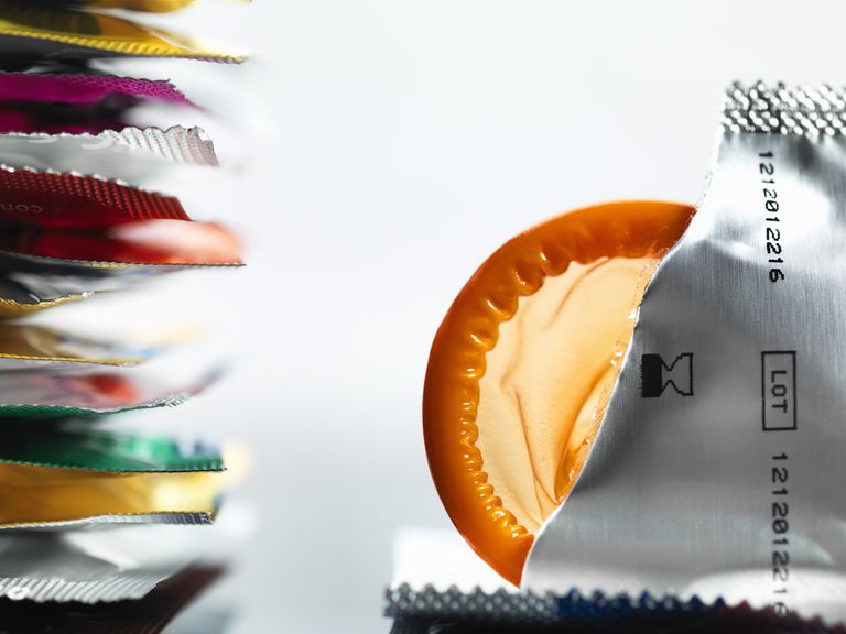 stack of condom packets with a torn open packet and orange condom