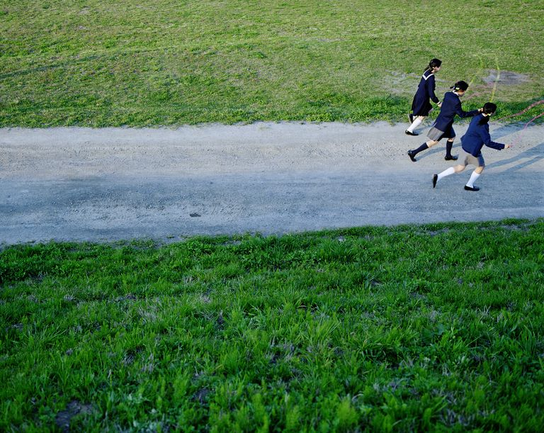 three girls in school uniforms running down a road