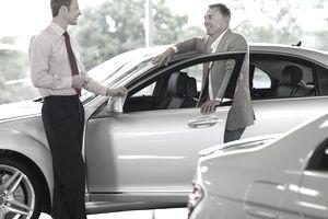 Salesman talking man in automobile showroom