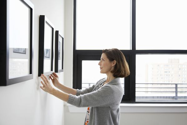 Woman adjusting picture frame at home