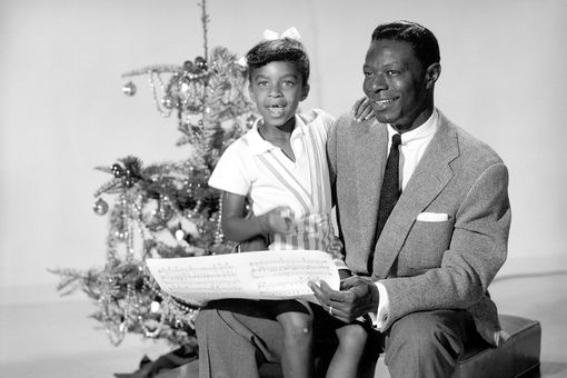 Singer Nat 'King' Cole and his daughter Natalie Cole pose for a portrait session in front of a Christmas tree in circa 1955