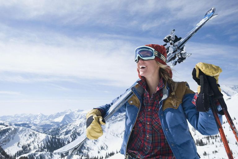 Woman holding skis on shoulder